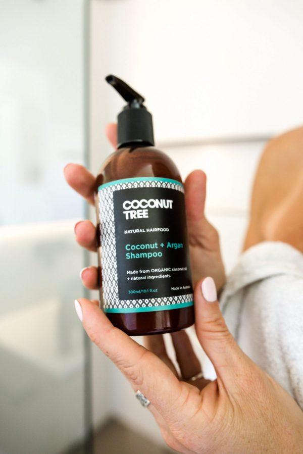 girl holding shampoo in shower